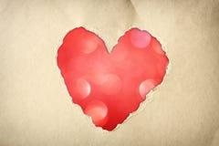 由在闪烁boke柔光的被撕毁的纸做的桃红色心脏形状。 免版税图库摄影