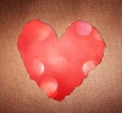 由在闪烁boke柔光的被撕毁的纸做的桃红色心脏形状。 图库摄影