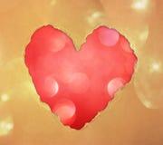 由在闪烁boke柔光的被撕毁的纸做的红色心脏形状。 库存照片