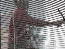 由在高层建筑物的绳索通入弄脏人干净的玻璃窗 免版税图库摄影