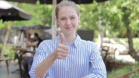 由坐在咖啡馆大阳台的年轻女人的赞许 股票录像