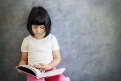 由墙壁的逗人喜爱的黑发小女孩阅读书 库存图片