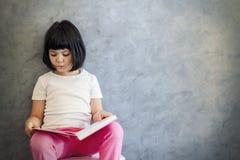 由墙壁的逗人喜爱的黑发小女孩阅读书 免版税库存照片