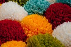 由多彩多姿的手工制造毛线做的绒球席子  库存照片