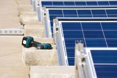 由太阳电池板屋顶平台建筑的钻眼工人 库存照片