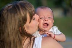 由她的母亲抱着的哭泣的婴孩 免版税库存照片