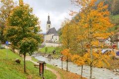 由小河和一个木桥的美丽的秋天槭树在有有雾的山的一个教会前面在遥远的背景中 图库摄影