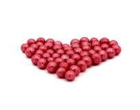 由小的圆的糖果做的红色心脏被隔绝在白色背景 免版税库存图片