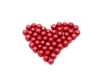 由小的圆的糖果做的红色心脏被隔绝在白色背景 免版税库存照片