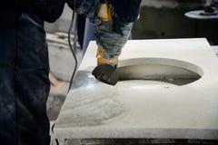 由小角度研磨机供以人员擦亮的大理石石桌 图库摄影