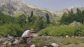 由山河供以人员从手的饮用水,当夏天高涨时 影视素材
