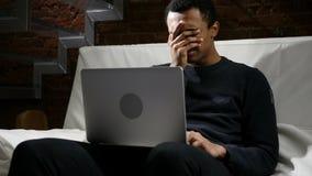 由工作,事务损失的非洲人翻倒在膝上型计算机的 免版税图库摄影