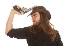 由帽子的牛仔长的头发举行手枪 免版税库存照片