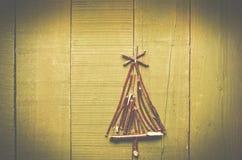 由干燥棍子做的圣诞树在木,明亮的backgroun 库存图片