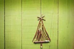 由干燥棍子做的圣诞树在木,明亮,绿色背景 库存照片