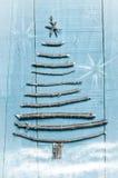 由干燥棍子做的圣诞树在木,蓝色背景 雪和雪高射炮图象 与星的圣诞树装饰品 图库摄影