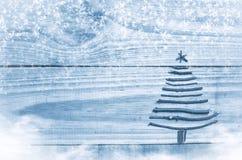 由干燥棍子做的圣诞树在木,蓝色背景 雪和雪高射炮图象 与星的圣诞树装饰品 库存图片