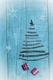 由干燥棍子做的圣诞树在木,蓝色背景 雪高射炮图象 圣诞树装饰品,工艺,礼物 免版税库存图片