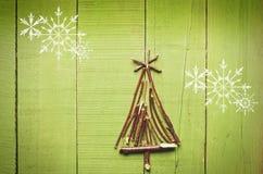 由干燥棍子做的圣诞树在木,绿色背景 雪高射炮图象 图库摄影