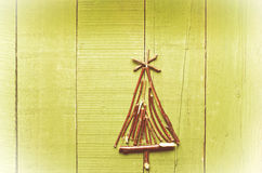 由干燥棍子做的圣诞树在木,绿色背景 免版税库存图片