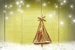 由干燥棍子做的圣诞树在木,绿色,多雪的明亮的背景 免版税库存图片