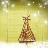 由干燥棍子做的圣诞树在木,绿色,多雪的明亮的背景 免版税库存照片