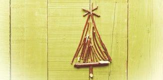 由干燥棍子做的圣诞树,在木,明亮的backgroun 免版税库存图片