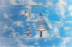 由干燥棍子和星做的两个圣诞树在木,蓝色背景 圣诞树装饰品,工艺 免版税库存照片