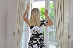 由庭院窗口的白肤金发的妇女 免版税库存照片