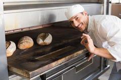 由开放烤箱的愉快的面包师 库存照片