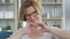由微笑的资深妇女的手工制造心脏姿态 股票录像