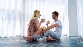 由愉快的夫妇的早晨咖啡在爱坐在光的地板 影视素材