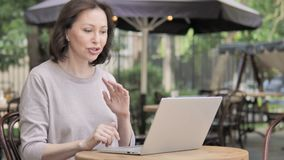 由愉快的老妇人的网上视频聊天,坐室外 股票录像