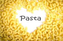 由意大利通心面面团的心脏形状在白色 免版税库存照片