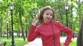 由成功的女性设计师的胜利标志红色皮夹克的,在绿园的画象 股票视频