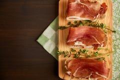 由手工制造黑麦面包和稀薄切好的新鲜的烟肉做的三明治 在一个木板的新鲜的绿色麝香草 在w的Succulend烟肉 免版税库存照片