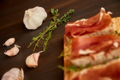 由手工制造黑麦面包和稀薄切好的新鲜的烟肉做的三明治 在一个木板的新鲜的绿色麝香草 在w的Succulend烟肉 免版税库存图片