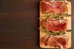由手工制造黑麦面包和稀薄切好的新鲜的烟肉做的三明治 在一个木板的新鲜的绿色麝香草 在w的Succulend烟肉 免版税图库摄影