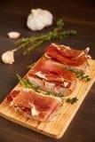 由手工制造黑麦面包和稀薄切好的新鲜的烟肉做的三明治 在一个木板的新鲜的绿色麝香草 在w的Succulend烟肉 库存图片