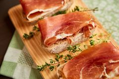 由手工制造黑麦面包和稀薄切好的新鲜的烟肉做的三明治 在一个木板的新鲜的绿色麝香草 在w的Succulend烟肉 库存照片
