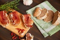 由手工制造黑麦面包和稀薄切好的新鲜的烟肉做的三明治 新鲜的绿色麝香草和热的红辣椒 在a的Succulend烟肉 免版税库存照片