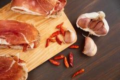 由手工制造黑麦面包和稀薄切好的新鲜的烟肉做的三明治 新鲜的绿色麝香草和热的红辣椒 在a的Succulend烟肉 图库摄影