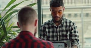 由手提电脑的年轻人摄影师博克的联机工作在咖啡馆 股票视频
