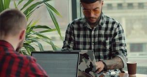 由手提电脑的年轻人摄影师博克的联机工作在咖啡馆 影视素材