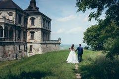 由手的走的新婚佳偶夫妇沿在老城堡附近的绿色草甸 美好的本质视图 后面看法  图库摄影