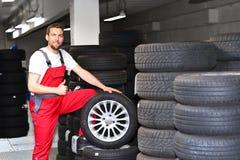 由技工装胎在汽车的变化在车间上 免版税库存图片
