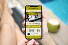 由拿着有app旅馆预定的水池的妇女电话 库存图片