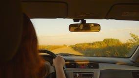 由摇晃的乡下公路的白种人女孩推进汽车 农村的横向 日落晚上在秋天 股票视频