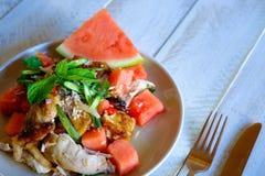 由新鲜的西瓜和新鲜的草本做的夏天沙拉与烤鸡大腿 关闭视图 图库摄影