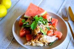 由新鲜的西瓜和新鲜的草本做的夏天沙拉与烤鸡大腿 库存照片